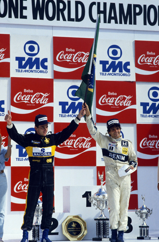 Jacarepagua, Rio de Janeiro, Brazil. 21-23 March 1986. Nelson Piquet (Williams Honda) and Ayrton Senna (Team Lotus) celebrate home drivers finishing in 1st and 2nd positions. World Copyright: LAT Photographic. Ref: Colour Transparency.